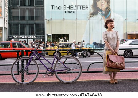 TOKYO, JAPAN - 26 JUNE 2016: Woman and bicycle against the railing of a busy sidewalk, in the busy shopping district of Shinjuku, Tokyo.