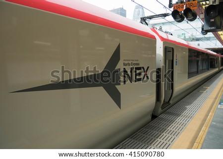 Tokyo, Japan - Mar 23, 2016 : Narita Express train at Shinjuku station with Cocoon tower background, Tokyo. Narita Express (NEX) is a fast train from Tokyo to Narita Airport. - stock photo