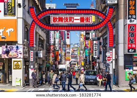 TOKYO, JAPAN - MARCH 15, 2014: Crowds walk below the Kabuki-cho signs. The area is a renown nightlife and red-light district. - stock photo