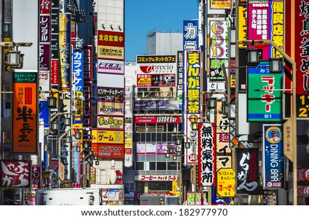 TOKYO, JAPAN - MARCH 15, 2014: Signs densely line an alleyway in Kabuki-cho. The area is a renown nightlife and red-light district. - stock photo