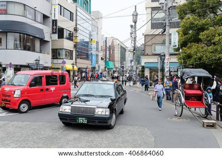 TOKYO, JAPAN-MARCH 30: Taxi and rickshaw waiting area near the kamakura station in Tokyo on MARCH 30, 2016 in Tokyo, Several taxi cabs are waiting in line along the sidewalk.The front of the station. - stock photo