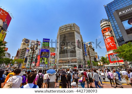 TOKYO, JAPAN - MAY 23, 2016: Pedestrians walk at Shibuya Crossing. The crossing is one of the world's most famous examples of a Scramble Crosswalk.