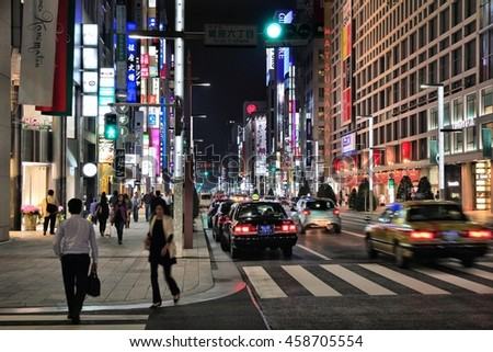 TOKYO, JAPAN - MAY 8, 2012: Shoppers visit night Ginza in Tokyo. Ginza is recognized as one of most luxurious shopping districts in the world, with many flagship luxury brand stores located here. - stock photo