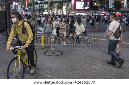 TOKYO, JAPAN - MAY 21ST, 2016. Crowd of people at the popular Shibuya Crossing junction at night time. Shibuya is a popular shopping district in Tokyo, Japan.