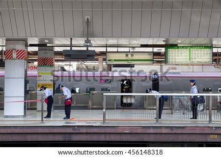TOKYO, JAPAN - MAY 19: Train service staff members lining up and bowing to the oncomming train,  at the Tokyo station on May 19, 2016 in Tokyo, Japan.