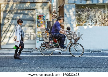 TOKYO, JAPAN - NOVEMBER 23: Japanese Family in Tokyo, Japan on November 23, 2013. Unidentified japanese father carries his children on a bicycle with baby seats - stock photo