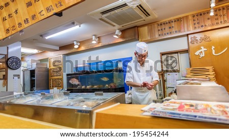 TOKYO, JAPAN - NOVEMBER 25: Japanese Sushi Chef  in Tokyo, Japan on November 25, 2013. Unidentified Japanese Sushi Chef prepares a dish of sushi for his customer
