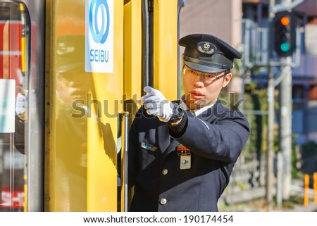 TOKYO, JAPAN - NOVEMBER 23: Train Conductor in Tokyo, Japan on November 23, 2013. Unidentified Japanese train conductor observes passenger before giving a sign to move the train - stock photo