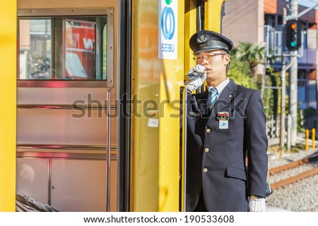 TOKYO, JAPAN - NOVEMBER 23: Train Conductor in Tokyo, Japan on November 23, 2013. Unidentified Japanese train conductor observes passenger before giving a sign to move the train