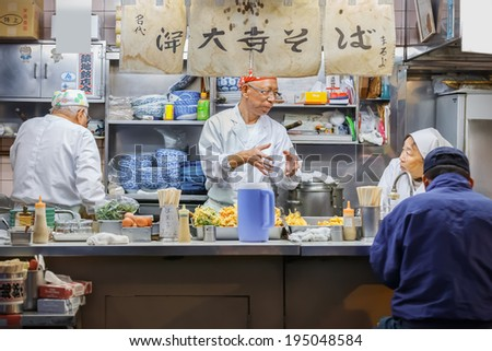 TOKYO, JAPAN - NOVEMBER 25: Tsukiji fish market in Tokyo, Japan on November 25, 2013. Japanese food stall openned early in the morning for people who purchases food here - stock photo