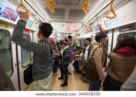 TOKYO, JAPAN - NOVEMBER 07, 2015: Unidentified people in subway train of Tokyo Metro pass. The transit system carries almost 8 million passengers a day. - stock photo
