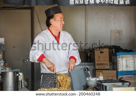 TOKYO, JAPAN - NOVEMBER 26: Yakisoba in Tokyo, Japan on November 26, 2013. Unidentified Japanese chef prepares a dish of Yakisoba fried noodle for his custumer