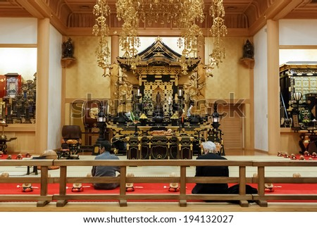 TOKYO, JAPAN - NOVEMBER 24: Zojoji Temple in Tokyo, Japan on November 24, 2013. Unidentified people pray inside the Ankokuden Hall in the Zojoji's Temple ground