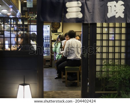 TOKYO, JAPAN - OCTOBER 12: Japanese businessmen eat and drink on a local restaurant on the narrow backstreet alleys around Shinjuku train station in Tokyo, Japan, on October 12, 2012. - stock photo