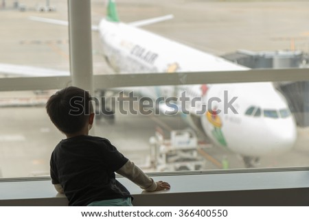 TOKYO, JAPAN - OCTOBER 16, 2013: One Boy look at Taiwanese Airline EVA Air Boeing B777 Airplane painted in Hello Kitty Global Jet theme livery dock Jet bridge at Narita International Airport (NRT) - stock photo