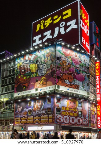 Tokyo, Japan - September 29, 2016: Night photo of a corner at an intersection near Shinjuku Station. Giant lighted billboards of cartoon and comic characters, neon signs, people and black sky.