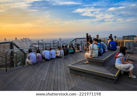 TOKYO - JUL 12: Tourists enjoy sunset at Roppongi Hills Mori Tower on Jul 12, 2014 Tokyo. It's the centerpiece of the Roppongi Hills urban development, currently the fifth-tallest building in Tokyo. - stock photo