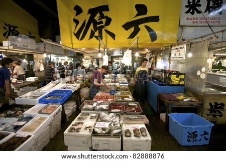 TOKYO - JULY 4: Seafood vendors at the Tsukiji Wholesale Seafood and Fish Market in Tokyo Japan on July 4, 2011. Tsukiji Market is the biggest wholesale fish and seafood market in the world. - stock photo