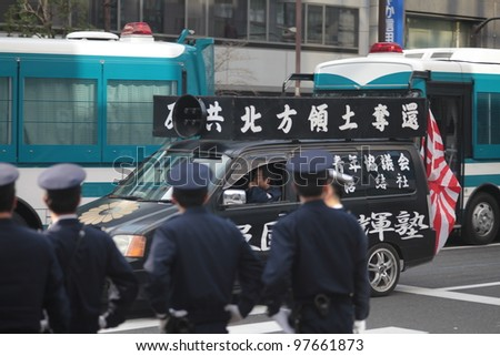 TOKYO - MARCH 11: Police stopping right-wing protesters near the Imperial Palace on March 11, 2012 in Japan. Radicals often use public holidays and anniversaries to promote nationalist propaganda.