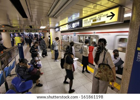 TOKYO - MAY 11: People wait in Tokyo Metro on May 11, 2012 in Tokyo. With more than 3.1 billion annual passenger rides, Tokyo subway system is the busiest worldwide. - stock photo