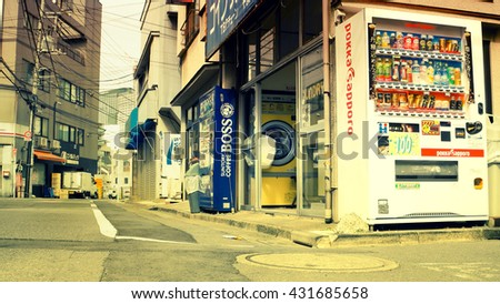 Tokyo - May 2016: Small lane with coin laundry and vending machine.  - stock photo