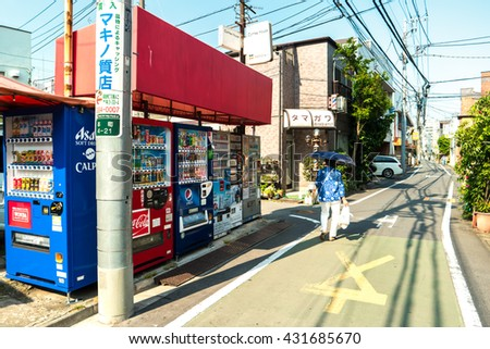 Tokyo - May 2016: Small lane with vending machines and lady with umbrella.  - stock photo