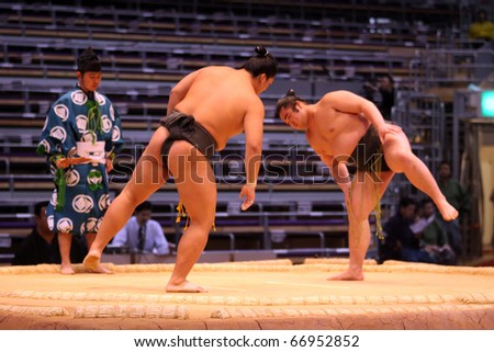 TOKYO - NOVEMBER 18: Two junior sumo wrestlers stretching before a fight in the Fukuoka Tournament on November 18, 2010 in Fukuoka, Japan. - stock photo