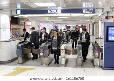 TOKYO -OCT 21 : people walking through a ticket gate in Shinjuku train station on 21 October 2013. Shinjuku is one of  the important  district with one of the biggest train station  in Japan. - stock photo