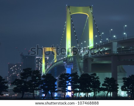 Tokyo Rainbow suspension bridge supports by night with scenic colourful illumination - stock photo