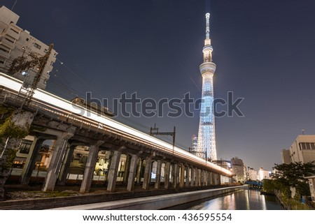 TOKYO SKYTREE - TOKYO - JAPAN - 11 JUN 2016 : Illuminated Tokyo Skytree (One of Famous Attraction in Tokyo) with local train light line on the train structure. - stock photo