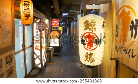 TOKYO, TOKYO, JAPAN AUGUST 5, 2014: Small alley located under the JR rail tracks. Several Izakayas are located on this place, marked by the lanterns hanging outside the shops.  - stock photo