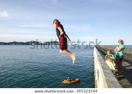 TOLAGA BAY, NZ - JAN 12: Youngsters jumping from the pier at Tolago Bay near Gisborne in New Zealand on January 12 2014.  Tolaga Bay is a popular summer destination for tourists
