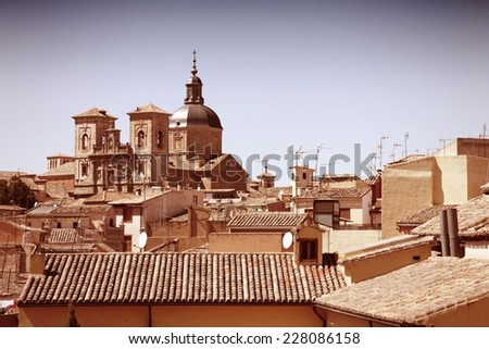 Toledo - Jesuit Church towering above the old cityscape. Spain, Europe. Cross processed color tone - retro filtered style. - stock photo