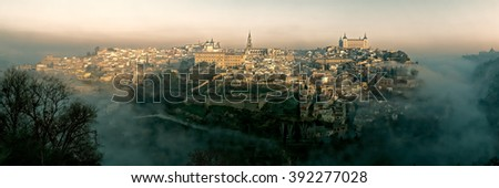 Toledo sits above the plains of Castilla-La Mancha in central Spain and is surrounded by the Tagus River. The valley was covered in fog during my visit. Dominating the skyline is the Gothic cathedral. - stock photo