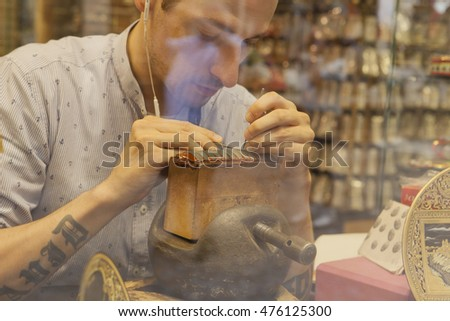 Toledo, Spain - July 28, 2016: goldsmith working on damascening piece through the shop window in historic center of Toledo, Spain