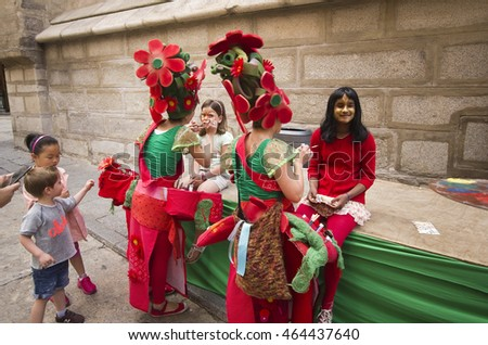 Toledo, Spain - May 28, 2016: Children have their faces painted by women dressed as flowers at the Corpus Christi festival in Toledo, Spain on May 28, 2016