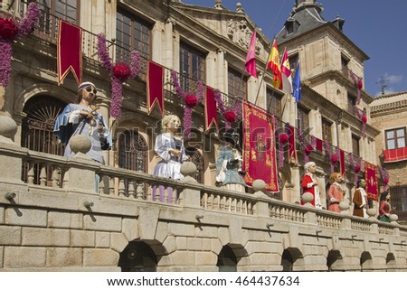 Toledo, Spain - May 28, 2016: Giant puppets (gigantes) of the Corpus Christi festival stand in front of the historical town hall decorated with banners in Toledo, Spain on May 28, 2016