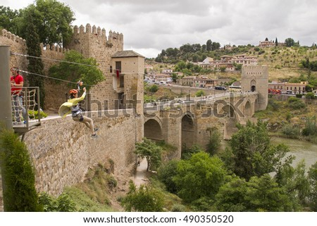 Toledo, Spain - May 28, 2016: Tourist girl crosses the river by rope next to the historical Puente de San Martin, or Saint Martins brdge, across the river Tagus in Toledo, Spain on May 28, 2016