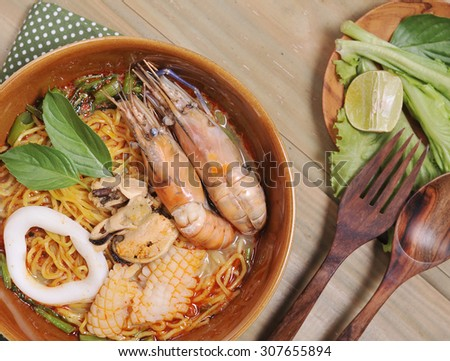 Tom Yam Kung soup with noodles , Tom Yum Nam Khon - Creamy Thai soup with prawns and mushrooms garnished with coriander leaves and served with lime wedges. Overhead shot. - stock photo