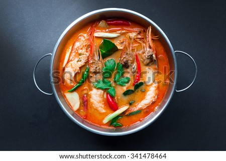 Tom Yum Goong,Thai Food in hot pot, top view on black background - stock photo