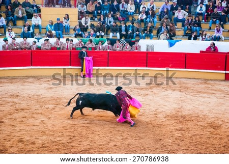 """TOMAR, PORTUGAL - OCTOBER 24: Cavaleiro fight with the bull and stabbing """"bandarilha"""" to the bull in portuguese style bullfighting in Tomar on October 24, 2010 - stock photo"""