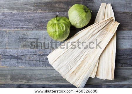 Tomatillos and corn husks on wooden surface with copy space.