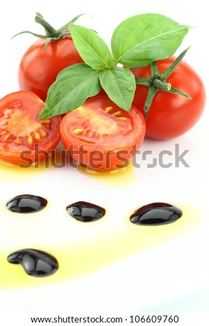Tomato and basil garnished with olive oil and balsamic vinegar - stock photo
