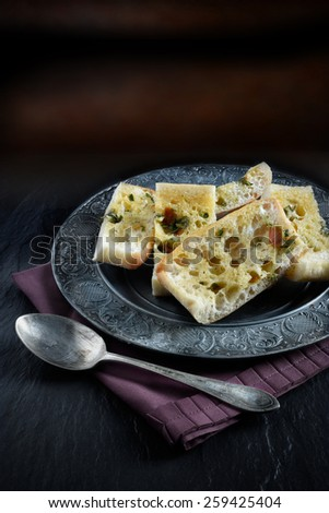 Tomato and Basil Olive Oil Ciabatta bread in a rustic setting against a dark background. Copy space. - stock photo