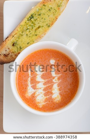 Tomato and carrot soup serve with garlic bread - stock photo