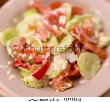 Tomato and cucumber salad with black papper and mayonnaise. Selective focus. Shallow depth of field. - stock photo