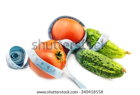 Tomato and cucumber wrapped in measuring tape on a white background