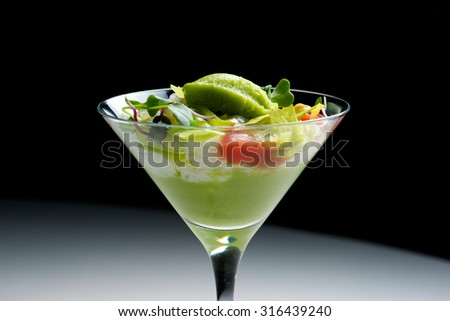 Tomato and green vegetables salad with cucumber cream served in crystal glass.