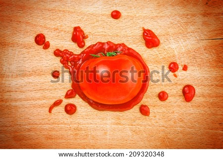 Tomato and ketchup on wooden plate board. Splattered tomato with ketchup on kitchen chopping board. - stock photo