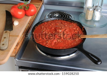 Tomato and Meat Spaghetti Sauce simmering in cast iron skillet atop Stainless Steel electric stove with tomatoes and garlic on cutting board with large kitchen knife. - stock photo